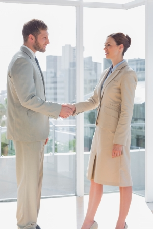 Man and woman in business suits shake hands